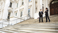 Two people in suits standing on the steps of a government building.